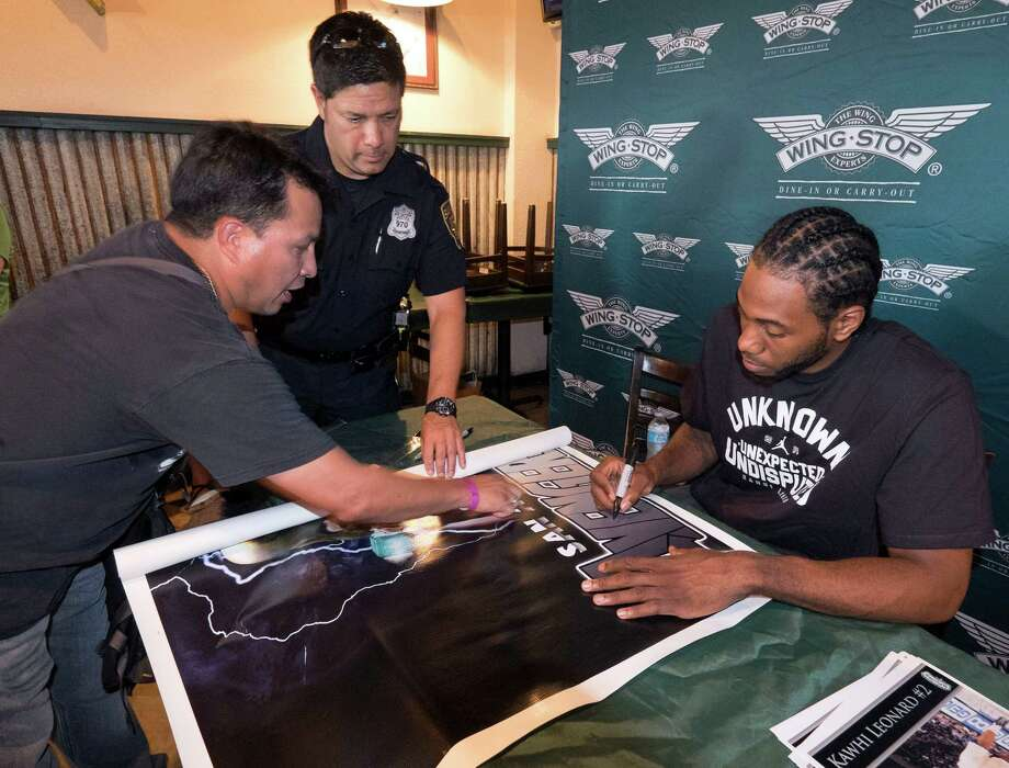 John De La Cruz, left, gets a poster signed by San Antonio Spurs guard Kawhi Leonard, Tuesday, July 15, 2014, in San Antonio. (Darren Abate/For the Express-News) Photo: Photo By Darren Abate/Express-News
