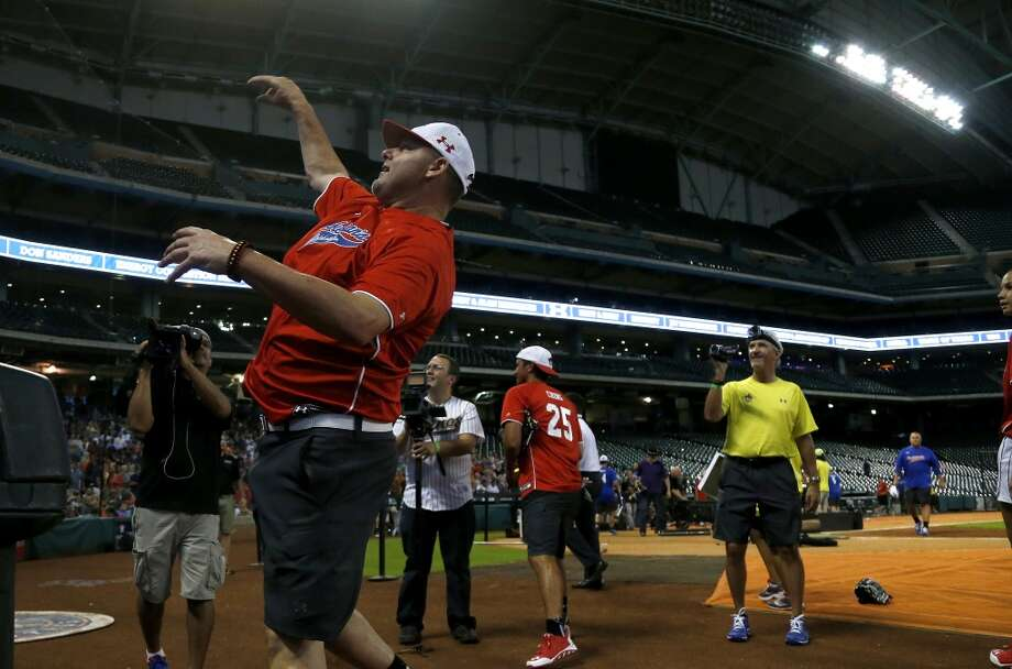 Roger Clemens throws softballs into the crowd. Photo: Karen Warren, Houston Chronicle