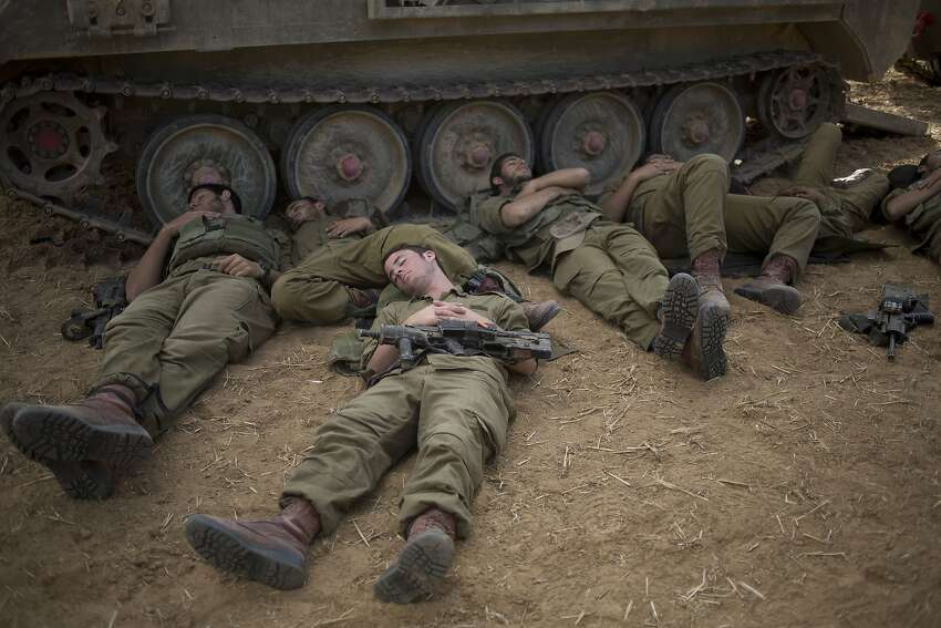 Israeli soldier sleep beside a military vehicle near the Israel Gaza Border, early Tuesday, July 15, 2014. The Israeli Cabinet has accepted an Egyptian proposal for a cease-fire to end a week of conflict with Hamas militants in the Gaza Strip that has killed 185 Palestinians and exposed millions of Israelis to Hamas rocket fire. No Israelis have been killed as a result of Hamas rocket launches. A senior Hamas official says the Palestinian militant group rejects an Egyptian proposal for a cease-fire with Israel. (AP Photo/Ariel Schalit)