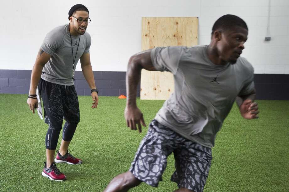 Abdul Foster works with Texans wide receiver Andre Johnson at IX Innovations on June 24. IX Innovations was recently opened by Foster, older brother of Texans running back Arian Foster. Photo: Brett Coomer, Houston Chronicle