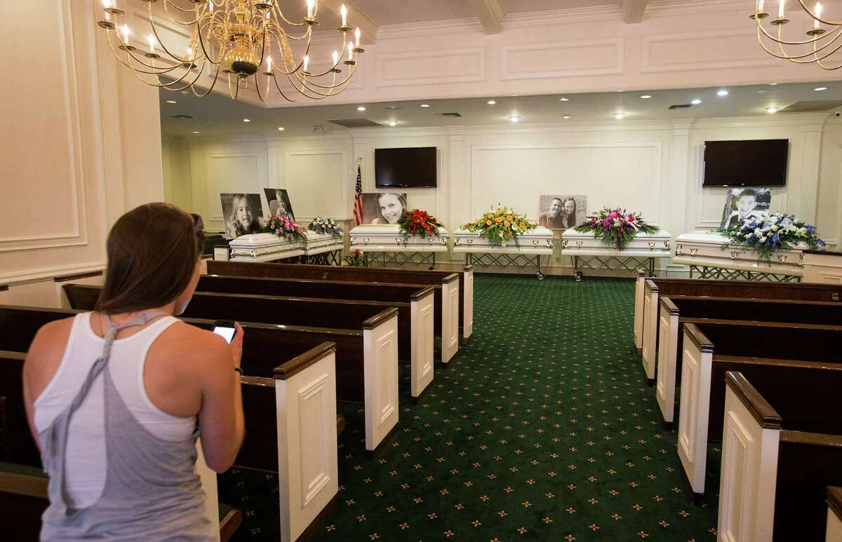 Jessica Gerland stands before the six caskets of the Stay family after delivering flowers before visitation at Klein Funeral Home Tuesday, July 15, 2014, in Houston.