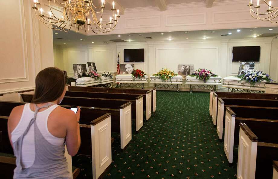 Jessica Gerland stands before the six caskets of the Stay family after delivering flowers before visitation at Klein Funeral Home Tuesday, July 15, 2014, in Houston. Photo: Brett Coomer, Houston Chronicle / © 2014 Houston Chronicle