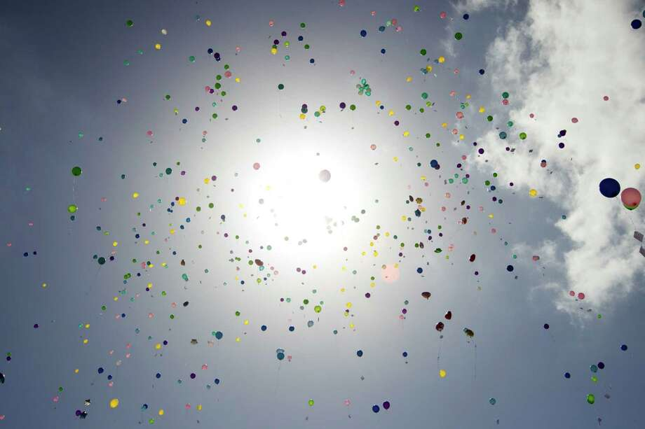 Balloons fly skyward during a community memorial celebrating the lives of the Stay family at Lemm Elementary School Saturday, July 12, 2014, in Spring. Photo: Brett Coomer, Houston Chronicle / © 2014 Houston Chronicle