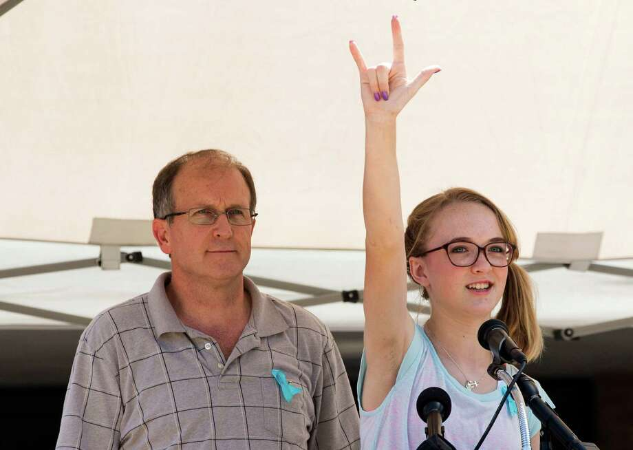 Cassidy Stay, right, lone survivor of the mass shooting of her parents and siblings, gestures to supporters after speaking at a community memorial celebrating the lives of the Stay family at Lemm Elementary School Saturday, July 12, 2014, in Spring. She is seated next to her uncle Drew Lyons. Photo: Brett Coomer, Houston Chronicle / © 2014 Houston Chronicle