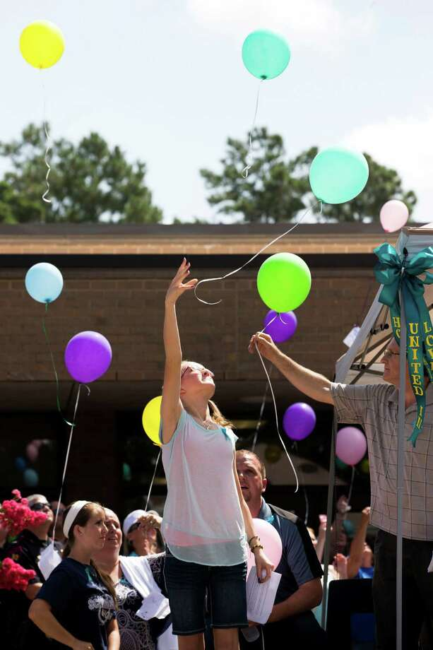 Cassidy Stay, lone survivor of the mass shooting of her parents and siblings, lets a balloon go during a community memorial celebrating the lives of the Stay family at Lemm Elementary School Saturday, July 12, 2014, in Spring. She is seated next to her uncle Drew Lyons. Photo: Brett Coomer, Houston Chronicle / © 2014 Houston Chronicle