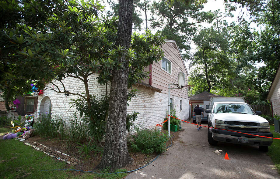A bio-remediation crew is seen at the home where seven people were shot, Friday, July 11, 2014, in Spring. The shooting took place Wednesday killing six people including four children and two adults, who were shot to death after an apparent domestic dispute. Photo: Cody Duty, Houston Chronicle / © 2014 Houston Chronicle