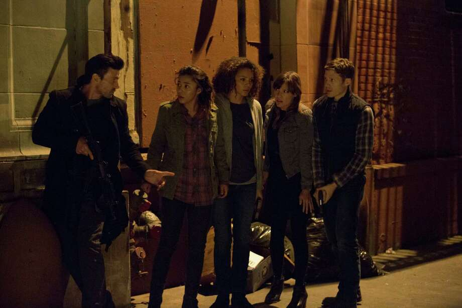 "Leo (Frank Grillo, from left) comes to the aid of Cali (Zoë Soul), Eva (Carmen Ejogo), Liz (Kiele Sanchez) and Shane (Zach Gilford) when the group is caught outdoors during the country's yearly 12 hours of anarchy in ""The Purge: Anarchy."" Photo: Justin Lubin / © Universal Pictures"