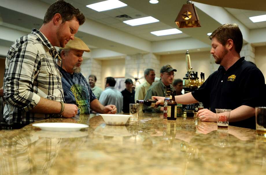 Tyler Blount waits on Jeff Wheeler to pour a taster of the St Arnold Brewing Company Bishops Barrel 2 at the Texas craft beer tasting at Del Papa Distributing Company on Thursday, February 21, 2013. Photo taken: Randy Edwards/The Enterprise
