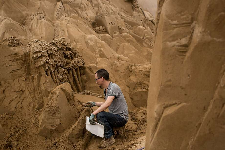 Sand sculptor Shao Jianxin of China works on sculpting a Panda at the site of Yokohama Sand Art Exhibition - Culture City of East Asia 2014 on July 16, 2014 in Yokohama, Japan. Producer and sand sculptor Katsuhiko Chaen invited artists from around the world including South Korea and China, to recreate the World Heritage and historical buildings in China, Japan and South Korea. The exhibition will be open from July 19 to November 3, 2014. Photo: Chris McGrath, Getty Images
