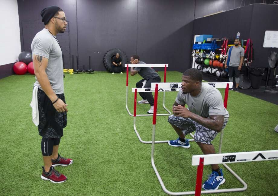 Abdul Foster, left, works with Texans wide receiver Andre Johnson. Photo: Brett Coomer, Houston Chronicle