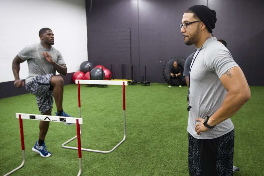 Abdul Foster works with Texans wide receiver Andre Johnson. Photo: Brett Coomer, Houston Chronicle