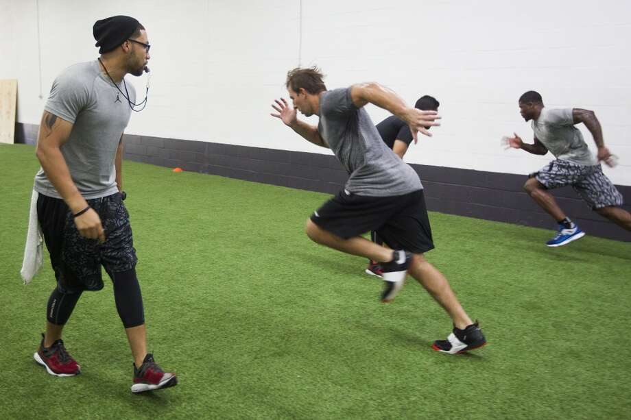 Abdul Foster, left, works with Owen Daniels, center, and Andre Johnson at his new gym, IX Innovations. Photo: Brett Coomer, Houston Chronicle