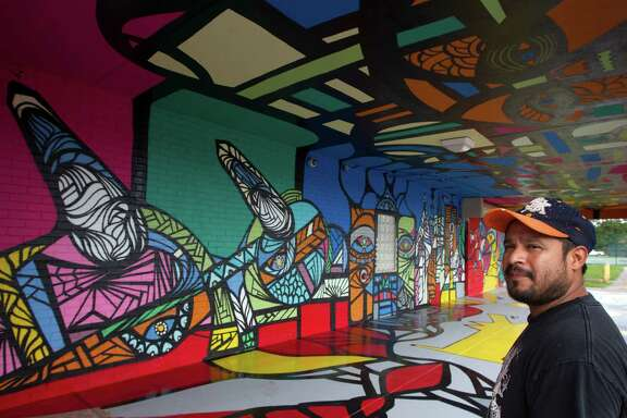 Daniel Anguilu poses for a portrait at the  Altharetta Yeargin Art Museum next to his mural that he has been creating on Tuesday, July 15, 2014, in Houston.