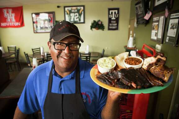 Ray Busch poses for portrait with the House Special at Ray's BBQ Shack.