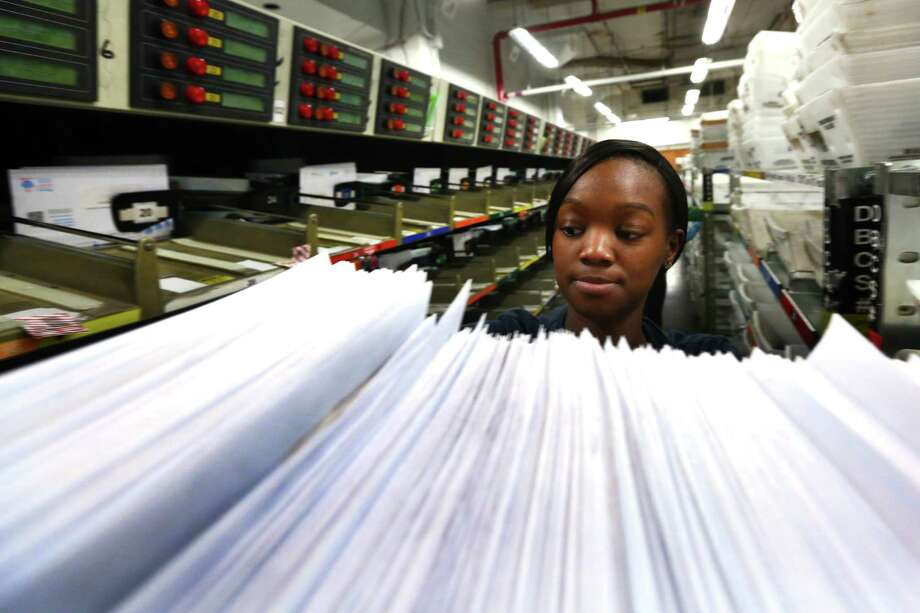Shemika Richard, 24, accommodates the letter mail sorted by zip code at the United States Postal Service Downtown Main in Houston, Thursday, Dec. 12, 2013. ( Marie D. De Jeséºs / Houston Chronicle ) Photo: Marie D. De Jeséºs, Staff / © 2013 Houston Chronicle