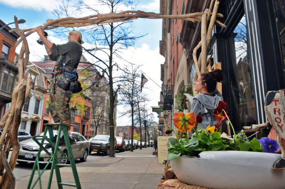 Daniel Killion, left, and Kate Hammill build a driftwood arbor in front of their Weathered Wood shop on 2nd Street Friday May 2, 2014, in Troy, NY.  (John Carl D'Annibale / Times Union) Photo: John Carl D'Annibale / 00026733A