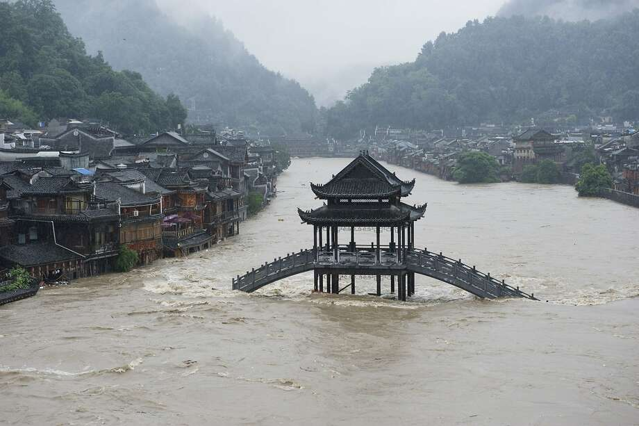 A bridge is submerged in floodwaters in the ancient town of Fenghuang in China's Hunan province. Rainstorms have affected more than 1 million people in the region. Photo: Str, AFP/Getty Images
