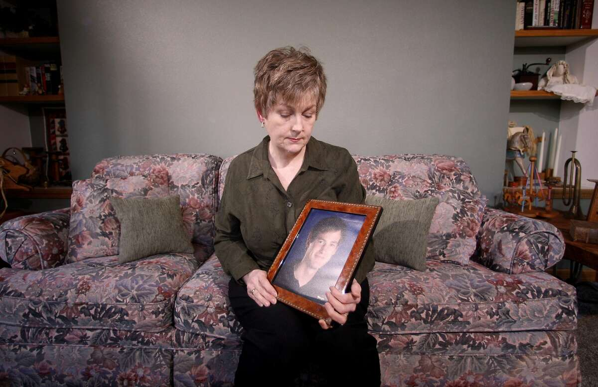 """FILE - This Monday, Feb. 27, 2012 file photo shows Karen Williams looking at a portrait of her son Loren Williams at her home in Beaverton, Ore. A group of influential lawyers says it has an answer to that pesky question of what should happen to your Facebook, Yahoo and other online accounts when you die. The Uniform Law Commission was expected on Wednesday to endorse a plan that would automatically give loved ones access to all digital accounts, unless otherwise specified in a will. The legislation would have to be adopted by individual state legislatures to become law. But if it does, the bill would make """"death switches"""" popular tools in estate planning, allowing people to decide which accounts should die when they do. """"This is something most people don't think of until they are faced with it. They have no idea what is about to be lost,"""" said Karen Williams of Beaverton, Oregon, who sued Facebook for access to her 22-year-old son Loren's account after he died in a 2005 motorcycle accident. (AP Photo/Rick Bowmer, File)"""