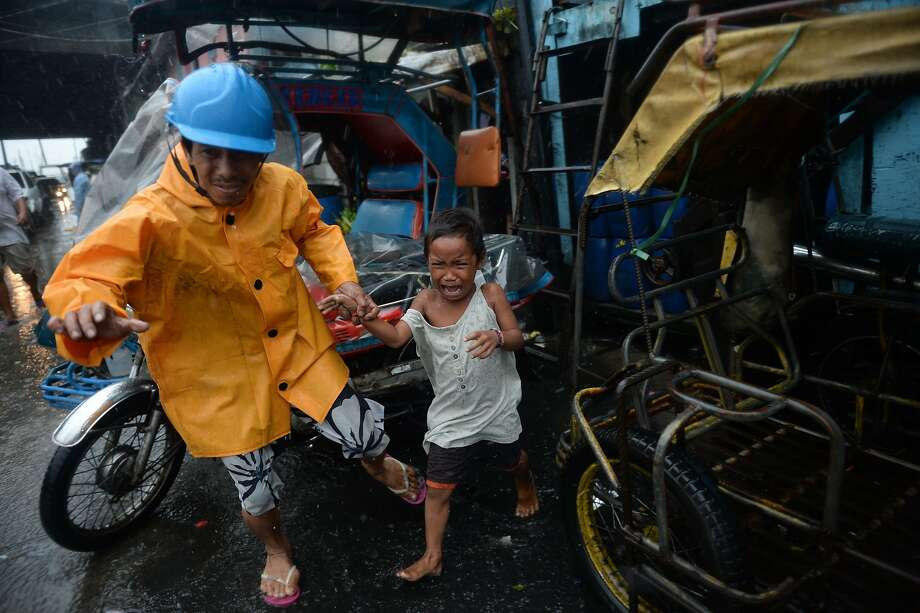 A village official helps a crying child evacuate to a safer area in Manila. The storm shut down the capital. Photo: Ted Aljibe, AFP/Getty Images