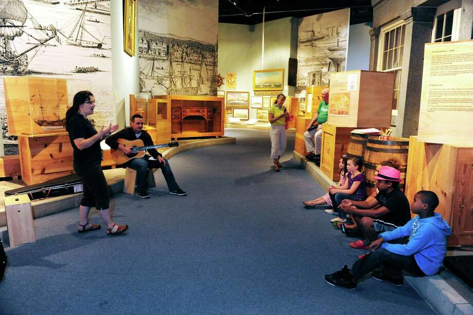 New York State Museum educators, Hatti Langsford, left, and Carl Morrone, second from left, sing a sea shanty work song with a group of children during a children's tour and art project at the New York State Museum on Wednesday, July 16, 2014, in Albany, N.Y.  Children took a tour of the Ports exhibit and learned old time sailing songs and then created paintings of a ship.   (Paul Buckowski / Times Union) Photo: Paul Buckowski / 00027783A