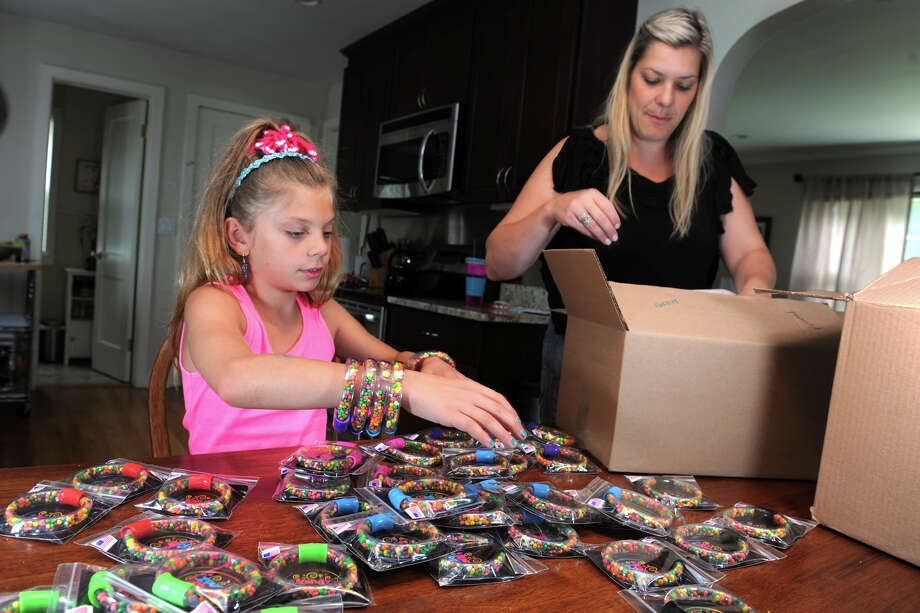 Samantha Sperrazza helps her mother Marisa sort and box a bunch of her ìkandy bandZî, the clear plastic bracelets filled with candy that she invented and debuted at the recent Invention Convention, in Danbury, Conn. July 16, 2014. They now have a patent pending on the bracelets, which are now for sale at area businesses. Photo: Ned Gerard / Connecticut Post