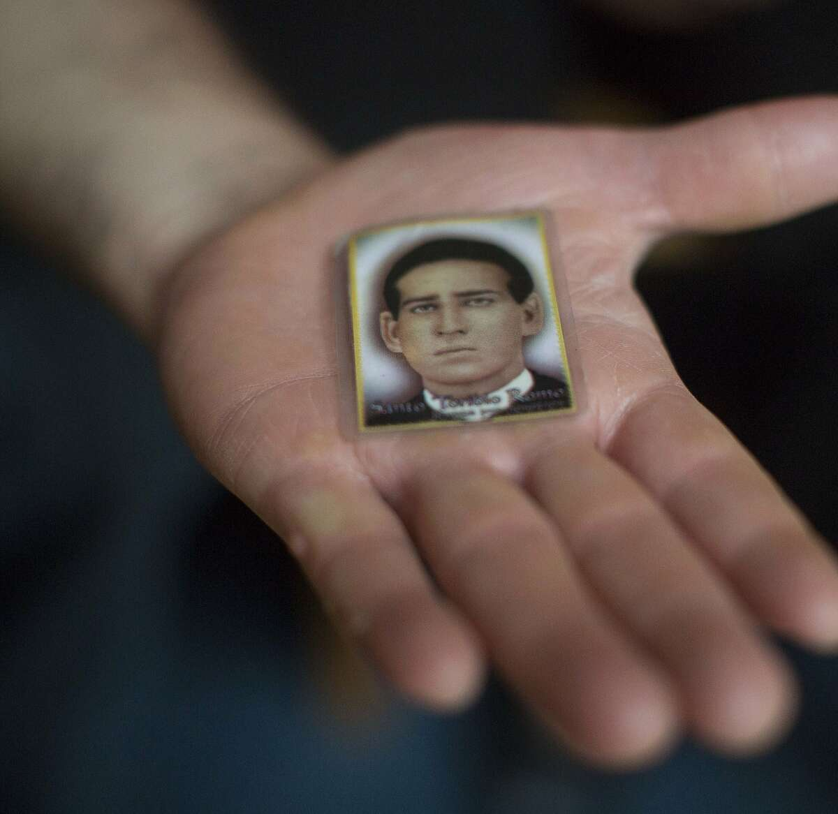 Jose Ochoa holds a photo of Santo Toribio Romo Gonzalez who some immigrants feel watches over them. (Rick Loomis/Los Angeles Times/MCT)