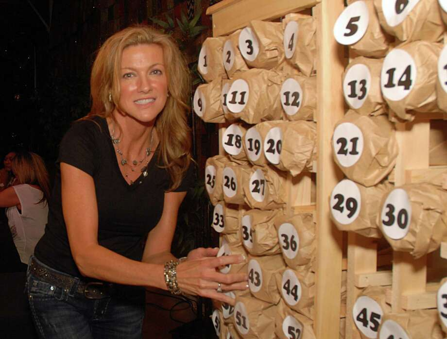 Pavilion Partners volunteer Caroline Garrett, of The Woodlands, pulls a numbered bag at the Wine Pull booth during the Cynthia Woods Mitchell Pavilion Partners Pre-Concert Dinner and Fundraiser in the House of Blues Hospitality Tent at the Pavilion. The event took place before the Lionel Ritichie, with CeeLo Green concert. Photograph by David Hopper Photo: David Hopper, For The Chronicle / freelance