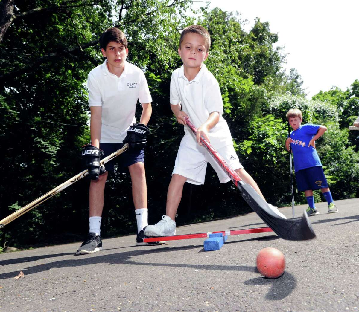 At center, Lucas St. Louis, 9, balances on a board while attempting stick handling skills with a ball as Mike Mozian, 16, of Greenwich, left, looks on during a hockey skills clinic taught by Mike and his brother Alex, 14, at the home of Jenny Allen of Old Greenwich, Conn., Wednesday afternoon, July 16, 2014. The brothers started their mobile hockey clinic with the help of their father, Joe Mozian, where they travel to people's homes and give them hockey lessons and training in the driveway. Lucas St. Louis's father is Greenwich resident and New York Ranger, Martin St. Louis. Jenny Allen's son, Kyle Allen, 8, at right, and other friends, also participated in the 90 minute clinic in the driveway of the Allen home.