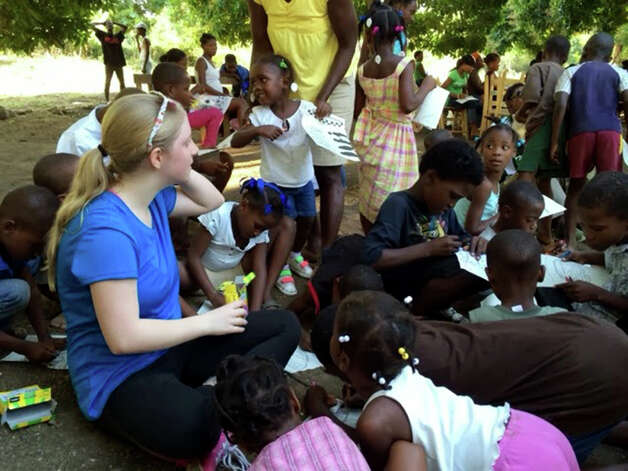 Jen Mosher, of Averill Park, works with Haitian children during Tech Valley High School?s trip to Haiti in January. The trip was a part of the community service element of student studies. Students at Tech Valley High School must undertake 100 hours of community service before graduating.