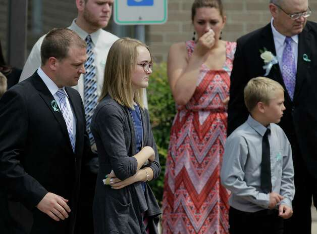 Cassidy Stay, second from left, leaves The Church of Jesus Christ of Latter-day Saints ,16331 Hafer Road, after the funeral service of six members of her family Wednesday, July 16, 2014. Photo: Melissa Phillip, Houston Chronicle / © 2014  Houston Chronicle
