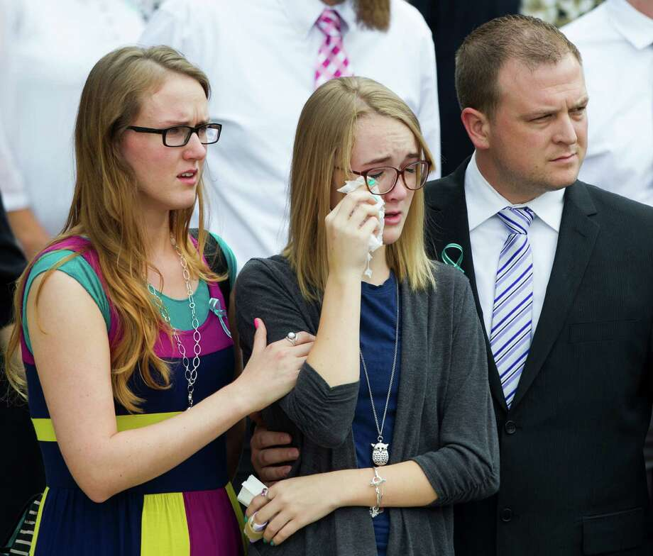 Cassidy Stay, the only member of her family to survive a mass shooting in Spring last month, leaves The Church of Jesus Christ of Latter-Day Saints with other mourners following funeral services for the six slain members of her family. Photo: Brett Coomer, Houston Chronicle / © 2014 Houston Chronicle