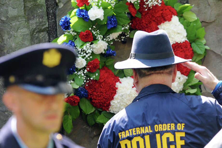 Stuart Levine of the state Parole Lodge Fraternal Order of Police, right, salutes a wreath placed at the Parole Officers Memorial during a ceremony on Wednesday, July 16, 2014, at the Empire State Plaza in Albany, N.Y. (Cindy Schultz / Times Union) Photo: Cindy Schultz, Albany Times Union / 00027818A