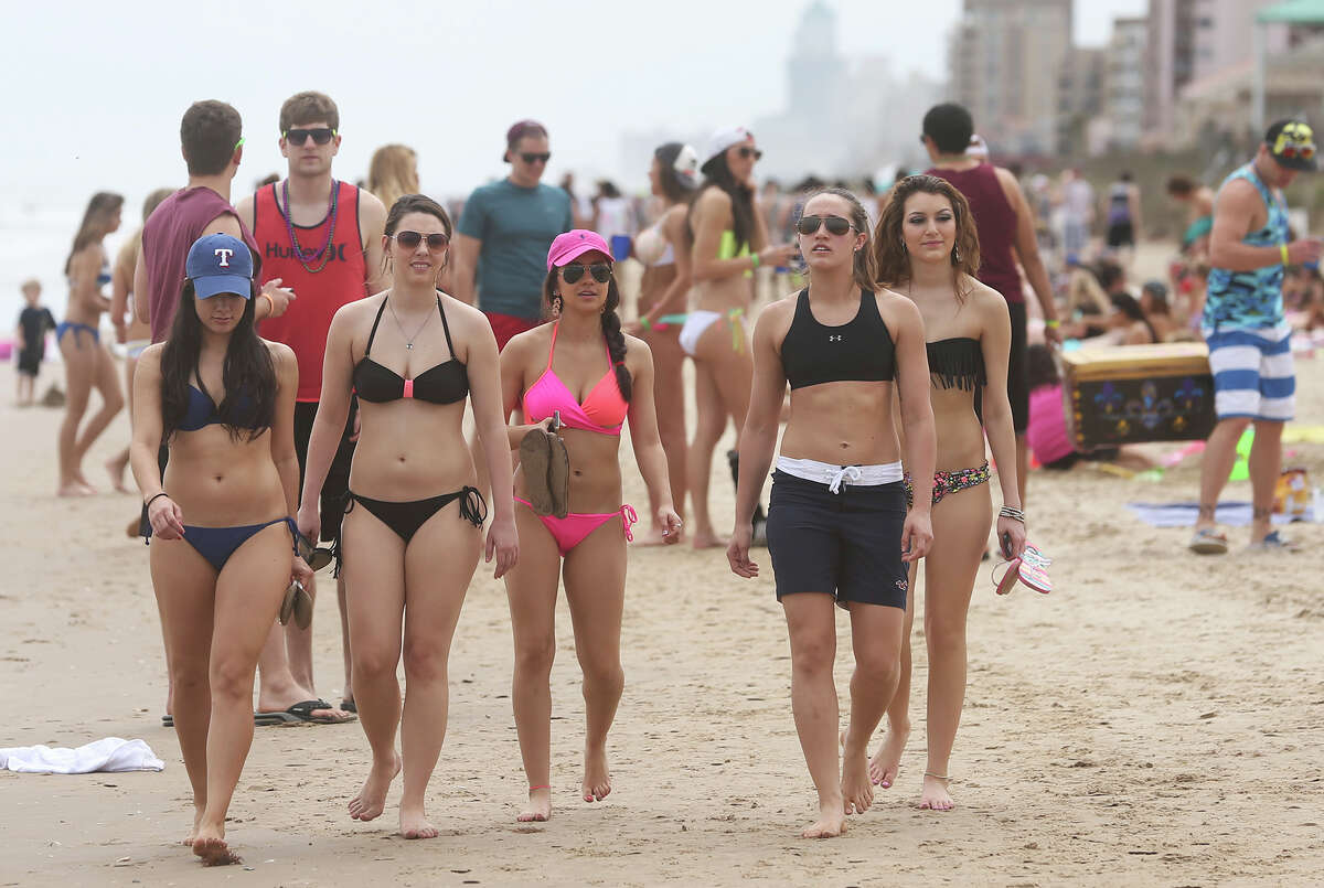 College students walk the sand during Spring Break 2014 on the South Padre Island beach near Clayton's on March 11, 2014.