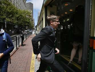San Francisco Cultural Affairs Director Thomas DeCaigny boards a Muni streetcar while on his way to a meeting at City Hall on July 01, 2014 in San Francisco, CA.