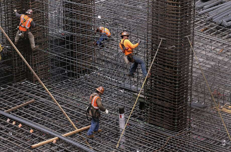 Construction workers connect rebar at a 126-unit apartment development at 1415 Mission St. at 10th Street. Photo: Michael Macor, The Chronicle