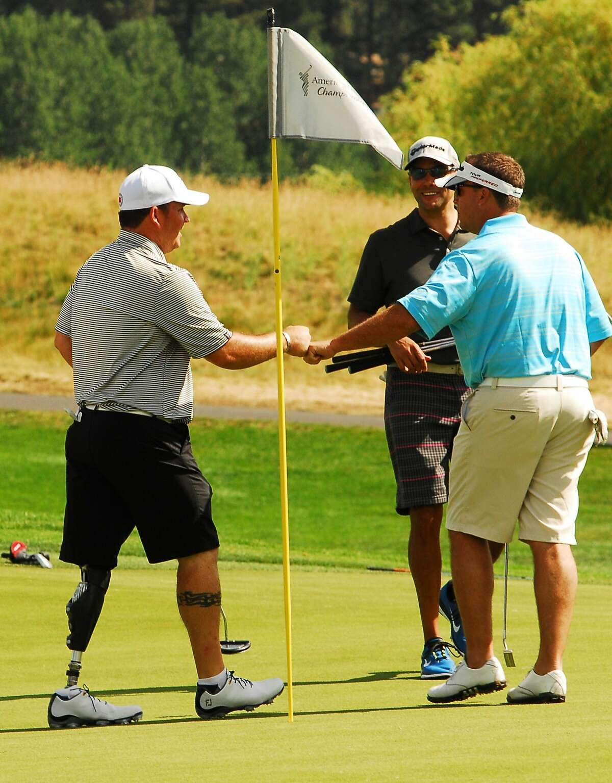 Wounded Warrior Chad Pfeifer gets a congratulatory fist bump from teammates during the Lake Tahoe Celebrity-Am on Tuesday July 15, 2014 in Stateline, Nevada.