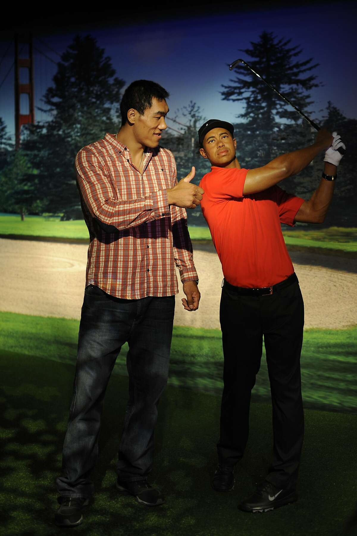Taishan Dong poses with a wax figure of Tiger Woods at Madame Tussauds on July 16, 2014 in San Francisco, CA. Taishan is a Chinese heavyweight boxer who will fight at the Longshoreman's Hall on July 18th.