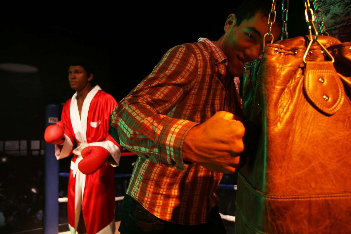 Taishan Dong pretends to strike a punching bag next to a wax figure of Muhammed Ali at Madame Tussauds on July 16, 2014 in San Francisco, CA. Taishan is a Chinese heavyweight boxer who will fight at the Longshoreman's Hall on July 18th.