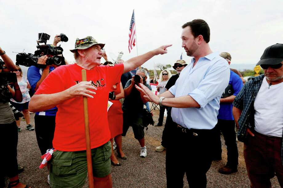 Adam Kwasman, a Tea Party patriot running for congress, has a heated discussion with an anti-immigration activist during a protest along Mt. Lemmon Road in anticipation of buses carrying  illegal immigrants on July 15, 2014 in Oracle, Arizona. See more photos from the crisis along the border and its roots. Photo: Sandy Huffaker, Getty Images / 2014 Getty Images