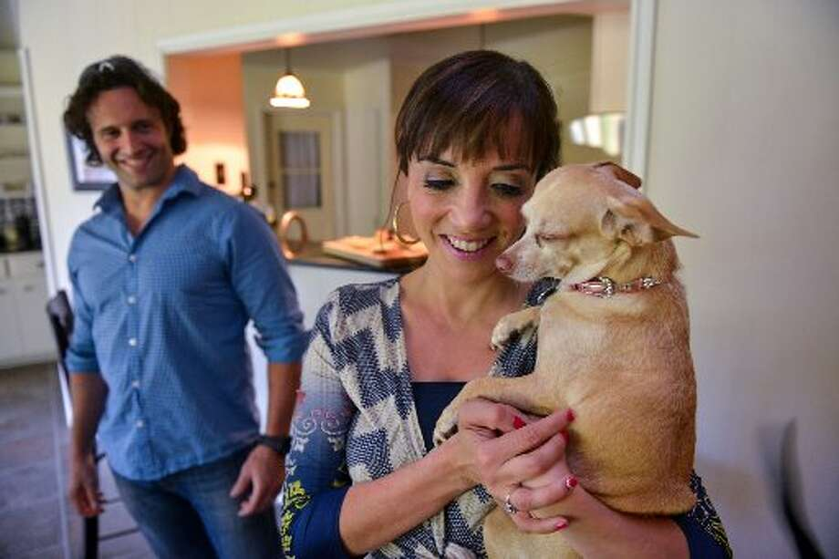 Marcella Della Casa hugs her chihuahua Lucy as husband Luca looks on during their Monday night stay-at-home dinners. Photo: Robin Jerstad, For The Express-News