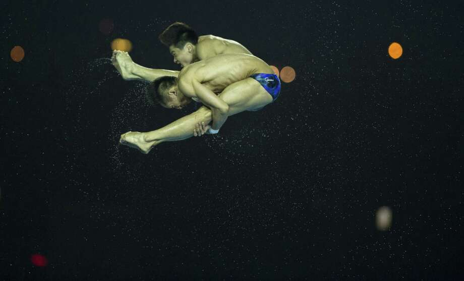 China's Lin Yue and Cao Yuan jump during the men's 10M Synchro Springboard Final during the 19th FINA Diving World Cup on July 16, 2014 in Shanghai. China won ahead of Germany (2nd) and USA (3rd).  Photo: JOHANNES EISELE, AFP/Getty Images / AFP