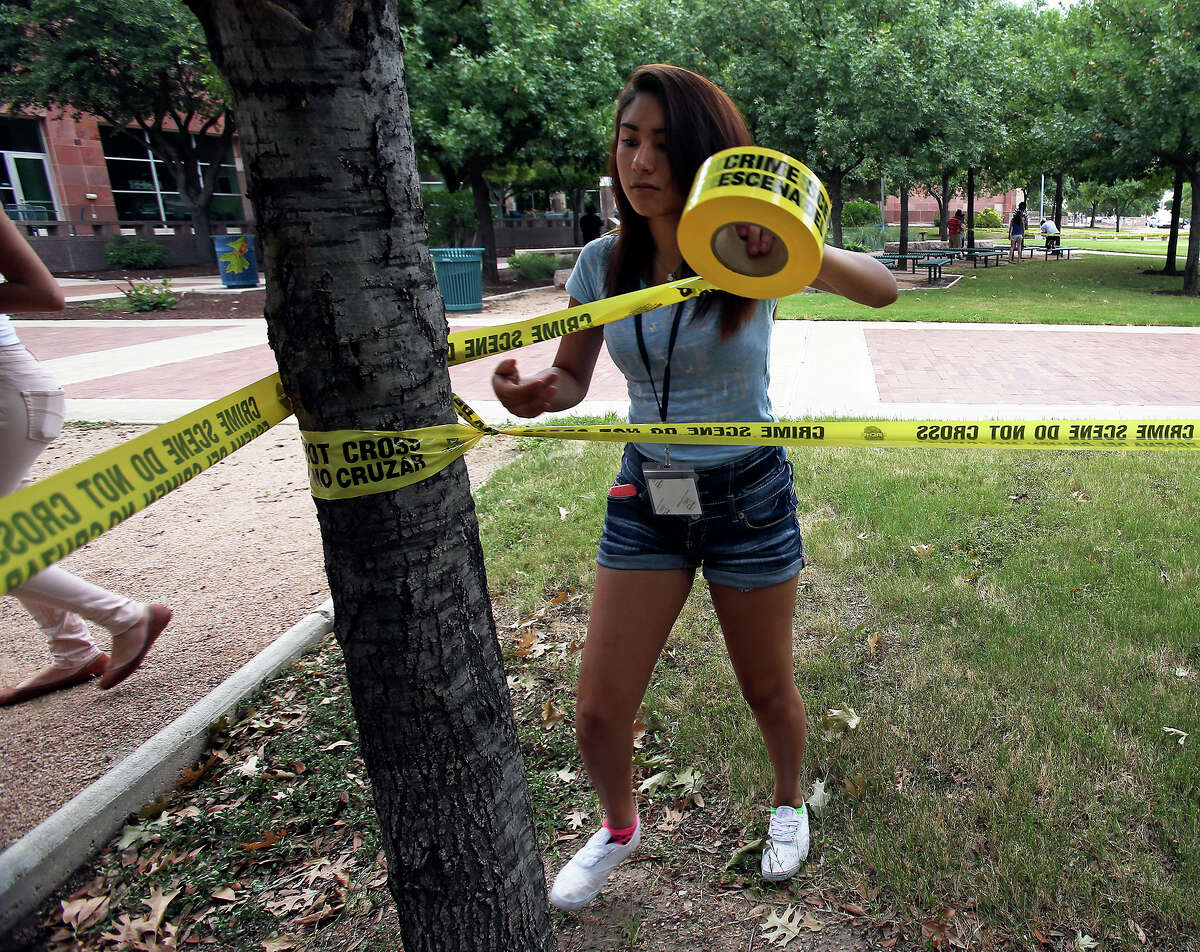 Lee High School junior Abigail Ozuna installs crime scene tape as UTSA Criminal Justice Summer Camp participants investigate mock crime scenes at the downtown campus during their week long summer camp on July 16, 2014.