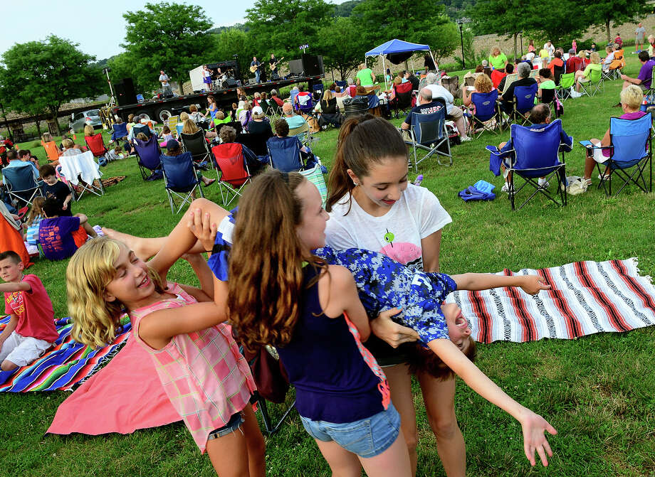"Alyssa Jardim, 9, left, Maura Carr, 10, and Lauren McKeon, 12, carry around their friend Logan Setlock, 8, as they dance to the music of The Highland Rovers as they perform during Shelton's ""Music Under the Stars"" concert series held at Riverwalk Park in Shelton, Conn. on Wednesday July 16, 2014. The next concert will be Gunsmoke on July 23rd from 7-9 p.m. Photo: Christian Abraham / Connecticut Post"