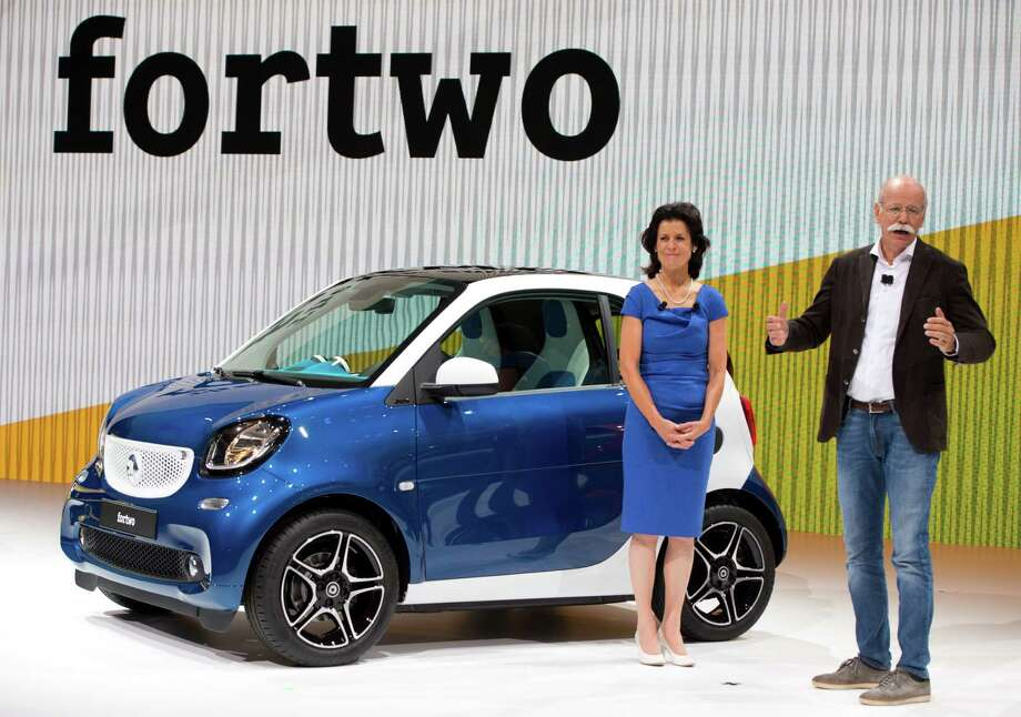Daimler CEO Dieter Zetsche, right, and Smart Automobile CEO Annette Winkler stand beside the new Smart fortwo during its world premiere in Berlin Wednesday, July 16, 2014. The new version is the same length at only 2.7 meters, or 8 feet, 10 inches, but is slightly wider and has a short front hood where the old one had none. (AP Photo/dpa, Soeren Stache) ORG XMIT: FOS101 Photo: Soeren Stache / dpa
