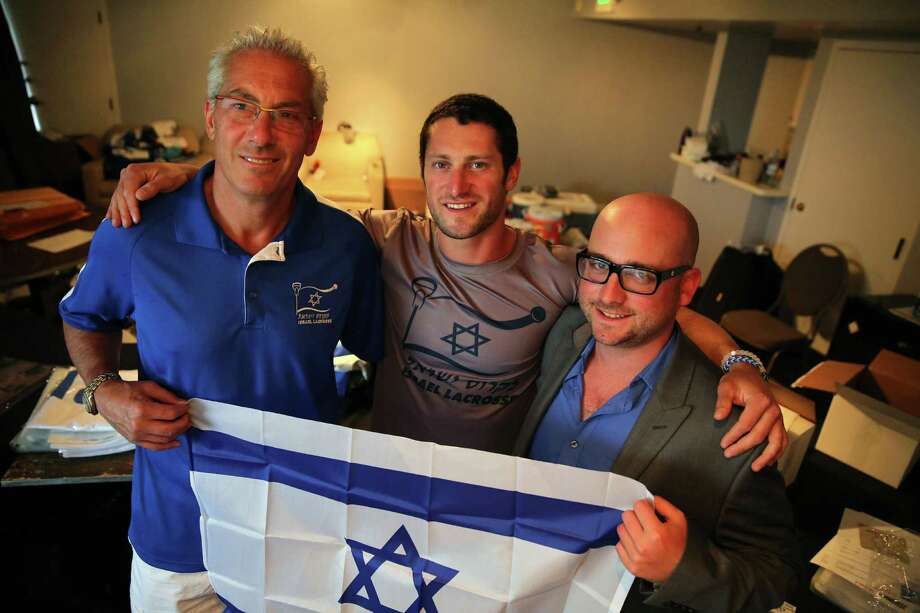 In this July 15, 2014 photo, Israel Lacrosse head coach Bill Beroza, left, attackman Noach Milller, center, and team executive director Scott Neiss hold an Israeli flag inside a hotel room used to organize team gear, in Commerce City, Colo. In its first tournament appearance, the Israeli lacrosse team is handily defeating opponents in the Lacrosse World Championship, even as its players' minds are on their homeland. (AP Photo/Brennan Linsley) ORG XMIT: COBL501 Photo: Breannan Linsley / AP