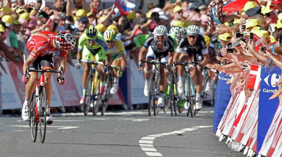 France's Tony Gallopin looks back to see if he has enough lead to stay ahead of the sprinting pack as he crosses the finish line to win the eleventh stage of the Tour de France cycling race over 187.5 kilometers (116.5 miles) with start in Besancon and finish in Oyonnax, France, Wednesday, July 16, 2014. (AP Photo/Peter Dejong) ORG XMIT: PDJ118 Photo: Peter Dejong / AP