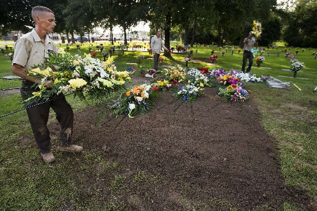 Paul Book, left, Jeremy Morin and Ronny Tubbs place flowers at the grave site of the Stay family after services at Klein Memorial Park on Wednesday in Tomball.