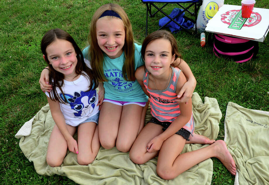 "Taylor Melanson, 8, left, sister Megan, 11, and friend Grace Pisanelli, 8, all of Shelton, hang out together as The Highland Rovers perform during Shelton's ""Music Under the Stars"" concert series held at Riverwalk Park in Shelton, Conn. on Wednesday July 16, 2014. The next concert will be Gunsmoke on July 23rd from 7-9 p.m. Photo: Christian Abraham / Connecticut Post"