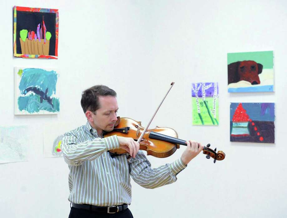 "Violinist,  David Creswell of the Chamber Players of the Greenwich Symphony Orchestra, practices in a side room before the ""Sounds for a Summer Night""  performance at the Greenwich Arts Council at 299 Greenwich Ave., in Greenwich, Conn., Wednesday night, July 16, 2014. The evening's program included Haydn, Medtner, Panufnik and Brahms. Photo: Bob Luckey / Greenwich Time"