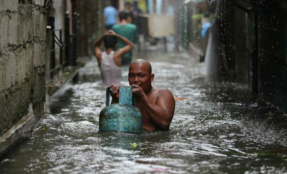 A man carries a propane tank while negotiating a flooded area as Typhoon Rammasun neared suburban Quezon City, northeast of Manila. The storm's eye made a late shift away from Manila. Photo: Aaron Favila / Associated Press / AP